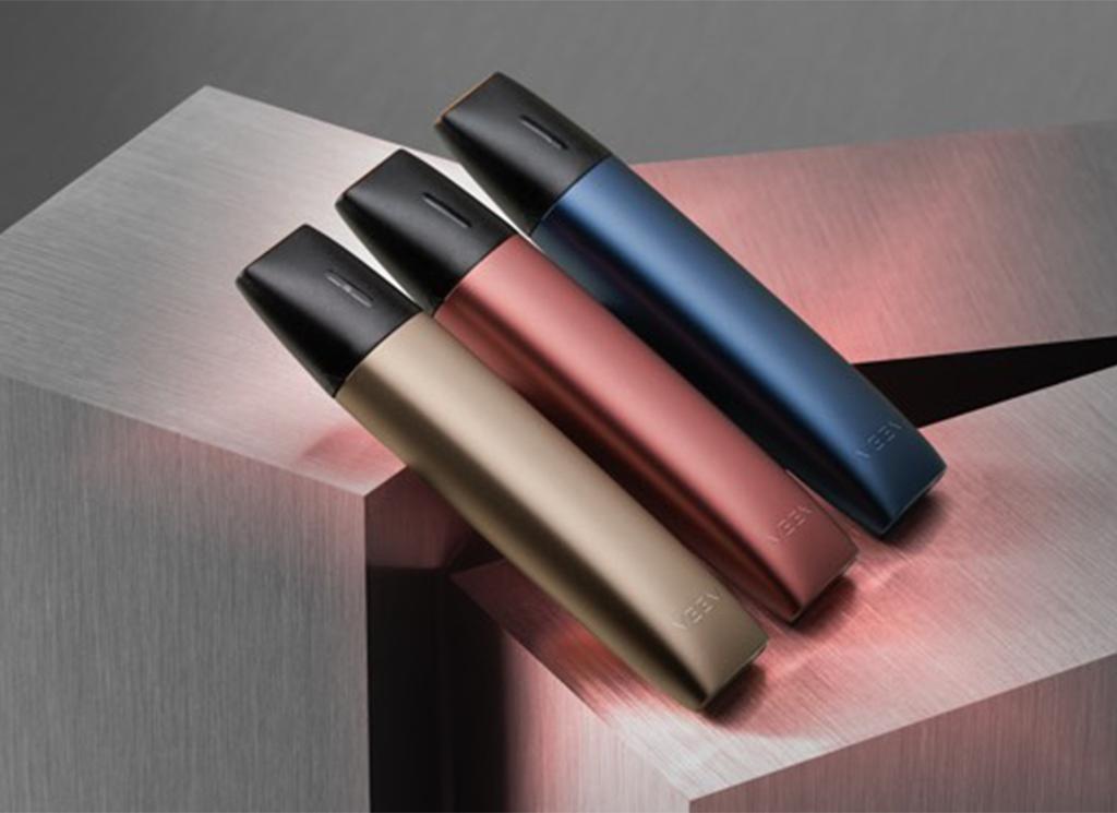 Trois appareils de vapotage VEEV de couleurs différentes sur des formes géométriques